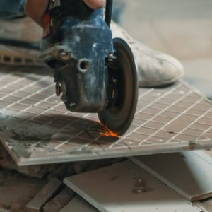 Worker cutting a tile using an angle grinder at construction site. Man worker cutting beige tile with a circular saw on a stool in kitchen floor. Concrete construction interior. Dirt. Copy space. Master in the jeans running on the machine to cut the tiles in the process of renovation of an apartment